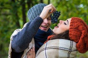 young couple eats grapes