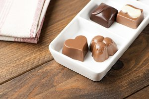 Chocolates with different shapes on white plate. Food.