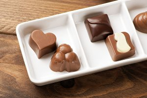 Delicious chocolates with different shapes on white plate. Food.