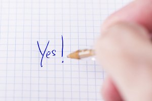 Male hand writes yes on sheet of paper.