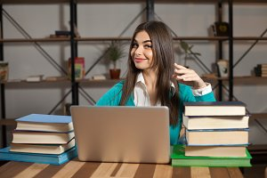 Woman with laptop and books
