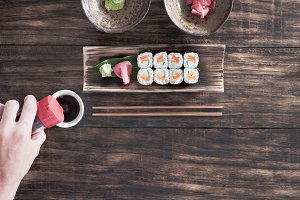 Sushi roll with salmon and cucumber in bamboo plate with soy sauce, wasabi and ginger on wooden desk. Top view.