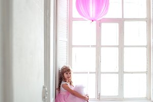 Girl with balloon in room
