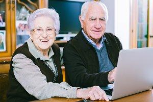 Senior couple using lap top at home