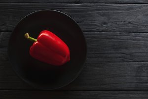 fresh red peppers on dark plate over old wooden textured background.