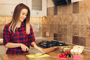 Young woman cutting bread in kitchen