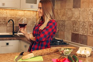 Beautiful girl in the kitchen with a glass of wine