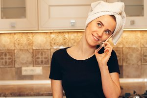 Young woman with a towel on her head talking on the phone