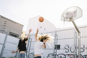 Girls jump for the ball, basketball