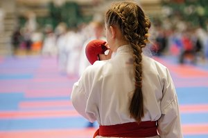 Sports kids - teenager girl sportsmen on karate use a protective mouthguard