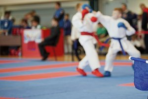 Martial art competitions - coach-judge with blue flag looking at karate teenager's fighting