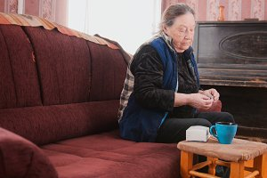 Senior lady - elderly woman at home takes the pills medication packages - healthcare