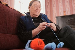 Old woman pensioner home - knits wool socks sitting on the sofa - elderly lady hobby