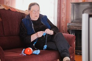 Old lady home at sofa - senior woman watching television and knits wool socks