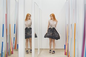Young woman trying dress near mirror in fitting room - shopping concept