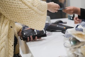 Woman paying by credit card in store - shopping concept