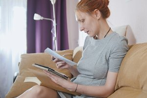 Portrait of young woman at home sitting at sofa and working with gadget and notebook