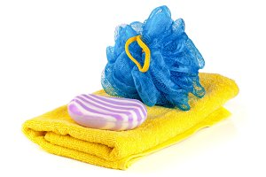Yellow towel with blue bath sponge and soap isolated on white background