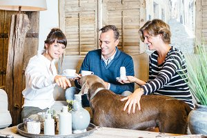 Couple with dog having tea with friend