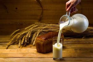 Milk from a glass jug poured into a glass, a loaf of rye bread, ears of corn on the background of wooden boards