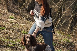 Beautiful woman brunette and brown cocker spaniel in the forest
