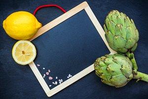 Organic fresh artichokes with lemon, copy space background