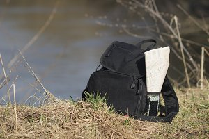 Backpack with phone and map in the pocket on the shore