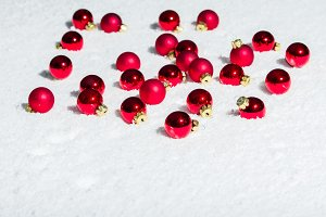 Red Christmas ornaments in snow