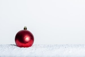 Red Christmas ornament in snow