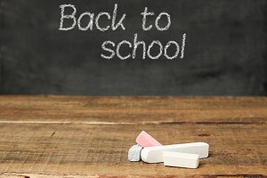 Pieces of chalk on a wooden background and chalkboard