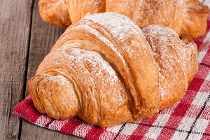 One croissant sprinkled with powdered sugar on a wooden table with napkin
