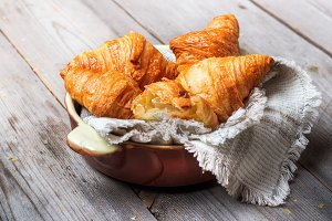 Fresh croissants for breakfast on rustic table