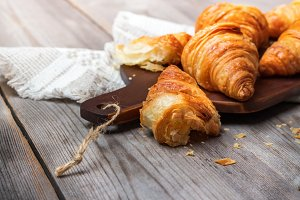 Fresh croissants for breakfast on cutting board rustic table