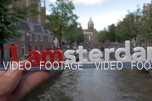 Amsterdam slogan and city view with canal