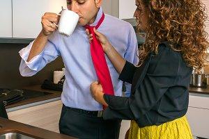 Woman adjusting tie of businessman at breakfast