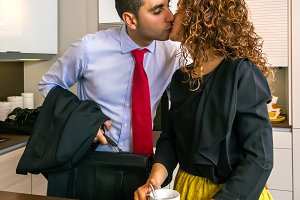 Busy businessman kissing to woman at breakfast