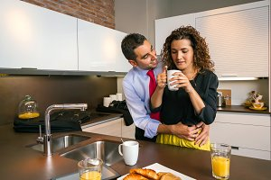 Happy businessman embracing to woman at breakfast