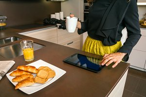 Woman using electronic tablet while having breakfast