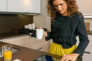 Woman looking electronic tablet while having breakfast