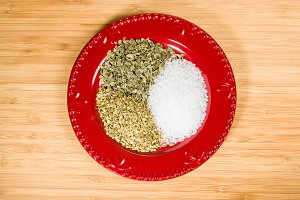 Spices and salt on red plate