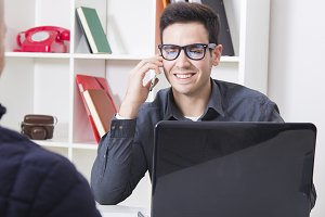 businessman smiling talking on the mobile phone with the client in the office