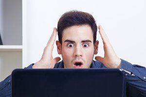 man with expression of surprise looking at the computer laptop at home or in the office