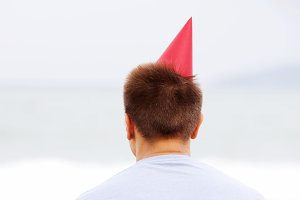 Guy in party hat near sea