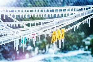Icicles on clothesline with clothesp