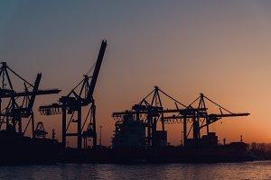 Sunset over Harbor Cranes in Hamburg