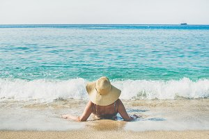 Woman lying on sand enjoying sea