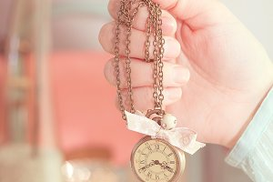 Girl hand holding vintage neck clock