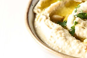Classic hummus with herbs, olive oil in a vintage ceramic bowl. Traditional Middle Eastern cuisine. Light white background.