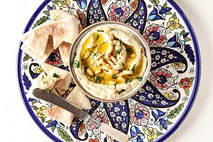 Classic hummus with herbs, olive oil in a vintage ceramic bowl and pita bread. Traditional Middle Eastern cuisine. Light white background.