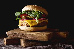 Fast food. Vegetarian burger with a chop, cucumber, tomato and lettuce. Tasty sandwich for lunch. Dark background.